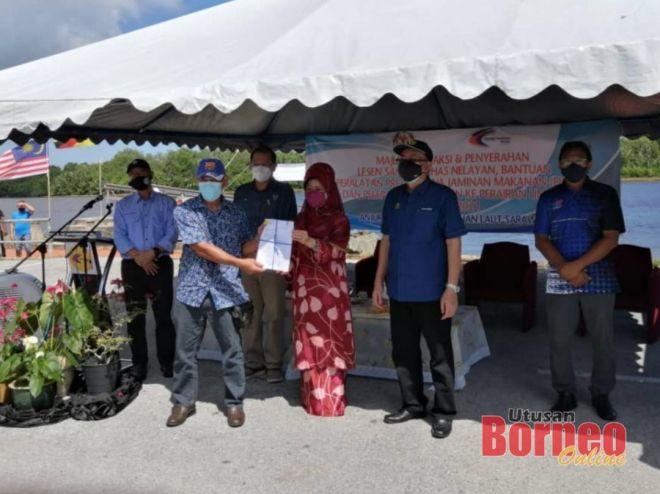 Fatimah (tiga kanan) ketika simbolik penyerahan lesen kepada 34 nelayan dalam majlos disaksikan Bohari (dua kanan) dan Aini (kanan).
