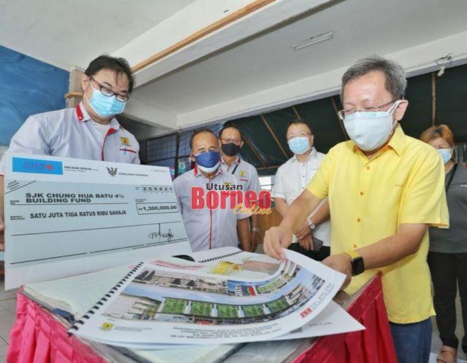 Dr Sim melihat dokumen projek pembinaan blok bilik darjah baharu empat tingkat SJKC Chung Hua Batu 4 1/2. -Gambar oleh Chimon Upon
