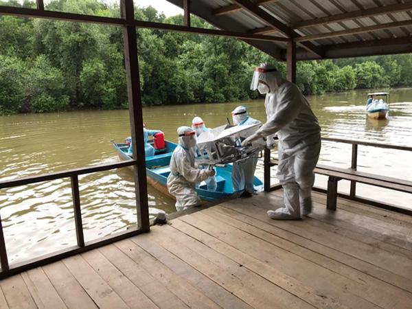 Petugas mengusung jenazah COVID-19 yang dibawa menggunakan bot melalui kawasan sungai.