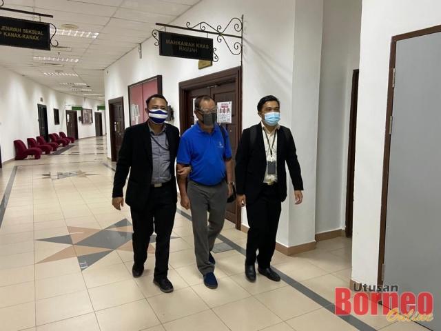 Lau (tengah) diiring pegawai SPRM semasa berada di Mahkamah Kuching, hari ini. - Gambar ihsan SPRM