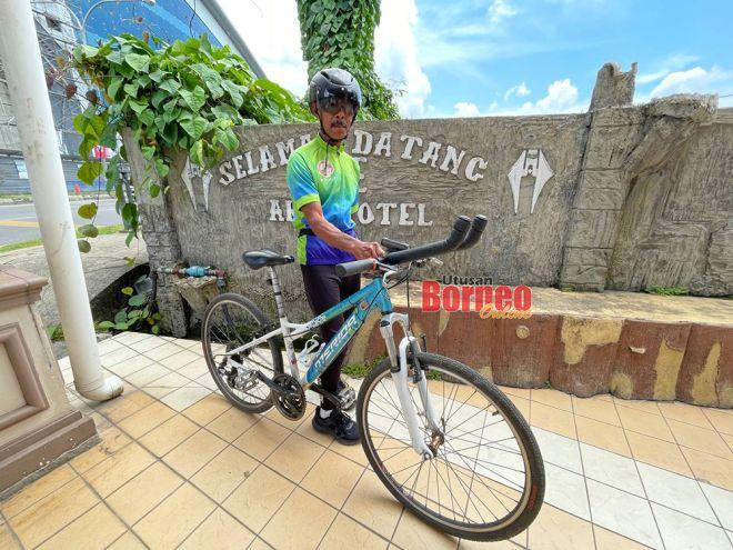 Awang Tinggal bergambar bersama basikal yang digunakannya dalam perjalanan dari Bintulu ke Kuching.