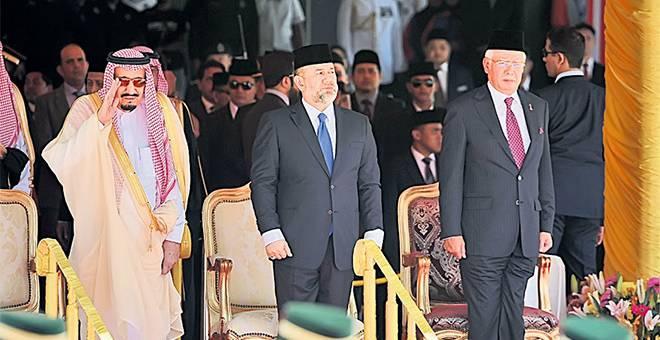 TABIK HORMAT: Raja Salman memberi tabik hormat pada sambutan rasmi lawatan negara empat hari ke Malaysia di Dataran Parlimen dekat Kuala Lumpur, semalam. Sultan Muhammad V turut berangkat menyambut ketibaan Raja Arab Saudi itu Turut kelihatan Najib (kanan). — Gambar Bernama