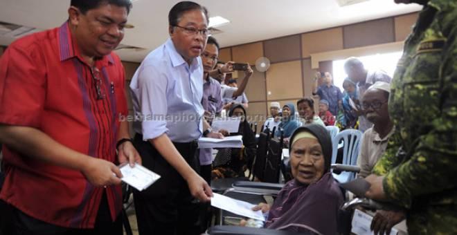 KERAJAAN PRIHATIN: Ismail Sabri (dua kiri) menyampaikan baucar Bantuan Rakyat 1Malaysia (BR1M) kepada warga emas Jamaiah Tamin, 86, seorang daripada penerima BR1M Parlimen Bera di Bera, semalam. — Gambar Bernama