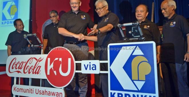 PELANCARAN: Hamzah (dua kiri) dan Ketua Pegawai Eksekutif Coca-Cola Bottlers (Malaysia) Sdn Bhd Stephen Lusk semasa melancarkan Program Keusahawanan Coca-Colaku bersama Kementerian Perdagangan Dalam Negeri, Koperasi dan Kepenggunaan (KPDNKK) di Putrajaya, semalam. — Gambar Bernama