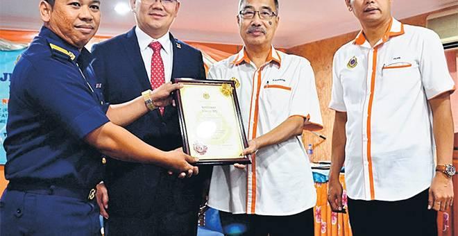 ANUGERAH: Kamarudin (tiga kiri) menyerahkan Anugerah Tokoh JPJ kepada Mohd Shaiful (kiri) selepas merasmikan Hari JPJ ke-71 peringkat negeri di Melaka, semalam. — Gambar Bernama