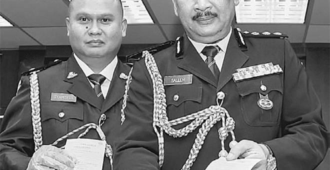 SIJIL PALSU: Mohd Salleh (tengah) menunjukkan sijil cuti palsu yang dirampas dalam tangkapan sindiket pemalsuan sijil cuti sakit di Ibu Pejabat Polis Kontinjen Johor, semalam. — Gambar Bernama