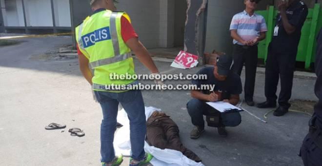 SIASAT: Anggota polis memeriksa keadaan mayat mangsa sementara siasatan lanjut dijalankan.