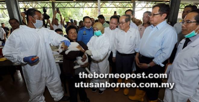 SAKSI: Abang Johari (dua kanan) melihat dengan dekat pegawai veterinar menyuntik vaksin pada seekor anjing semasa operasi pemvaksinan wabak rabies di Dewan Masyarakat Batu 10, Kuching semalam. Turut kelihatan Uggah (tiga kanan) dan Dr Sim (empat kanan).