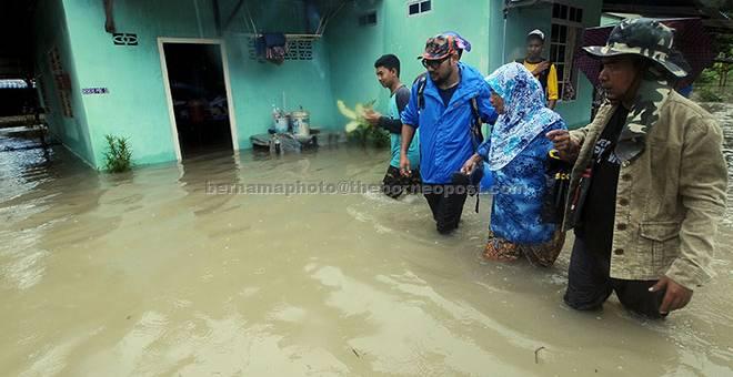 BANJIR: Penduduk kampung membantu seorang warga emas mengharungi banjir kilat berikutan hujan lebat di Kampung Kulup, Teluk Kumbar di George Town semalam. — Gambar Bernama