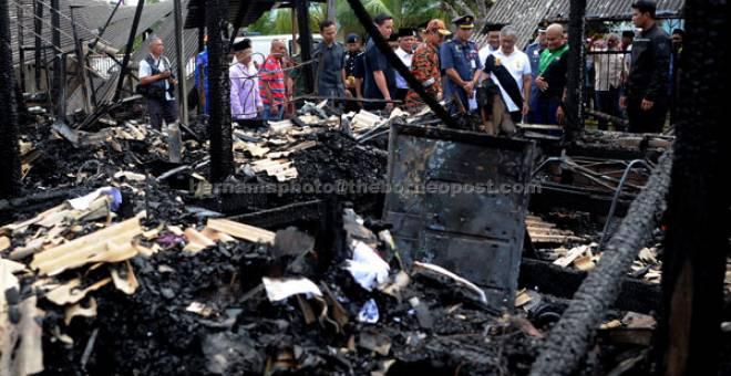 PRIHATIN: Tengku Abdullah (empat kanan) semalam melawat beberapa rumah yang musnah dalam kebakaran petang kelmarin                 di Kampung Sungai Isap di Kuantan. — Gambar Bernama