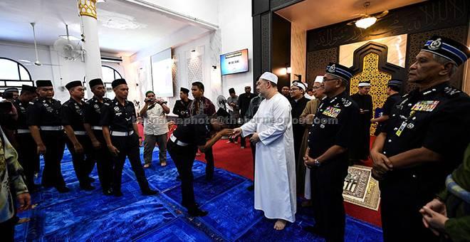 RAMAH MESRA: Sultan Muhammad V (tiga kanan) bersalam dengan sebahagian daripada anggota polis selepas selesai menunaikan solat Jumaat di Masjid Salehen, di Pulapol dekat Kuala Lumpur, semalam, sempena sambutan Peringatan Hari Polis yang ke-211 pada Ahad ini. — Gambar Bernama