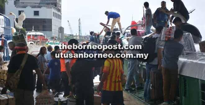 BALIK KAMPUNG: Penumpang bot ekspres sibuk menyimpan barang mereka di atas bot ekspres.