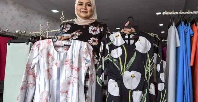 JAGA KUALITI: Alia memastikan material kain yang dijual di butiknya jenis sejuk, selesa dipakai dan tidak rasa melekit atau gatal pada badan bersesuaian dengan konsep 'minimalis', trend baju raya pada tahun ini. — Gambar Bernama