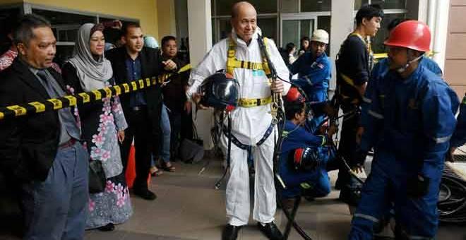 PATUHI PIAWAIAN: Lee memakai pakaian dan alat keselamatan ketika demonstrasi menggunakan peralatan perlindungan diri untuk operasi menyelamat di ruang terkurung atau sempit pada Program Keselamatan dan Kesihatan Pekerjaan untuk Pengamal Media di Ibu Pejabat NIOSH Wilayah Selatan, Taman Teknologi Johor semalam. — Gambar Bernama