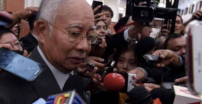 TENANG: Najib dikerumuni wartawan ketika keluar dari Dewan Rakyat di Parlimen semalam. — Gambar Bernama