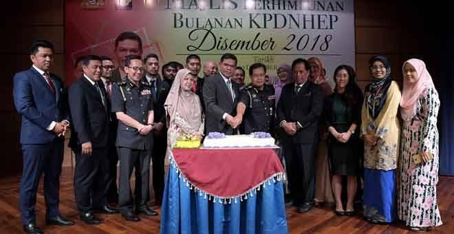 DIRAIKAN: Saifuddin (hadapan, lima kiri) memotong kek hari jadi bersama kakitangannya yang menyambut hari jadi bulan ini pada Perhimpunan Bulanan (KPDNHEP) bulan Disember di kementeriannya di Putrajaya semalam. — Gambar Bernama