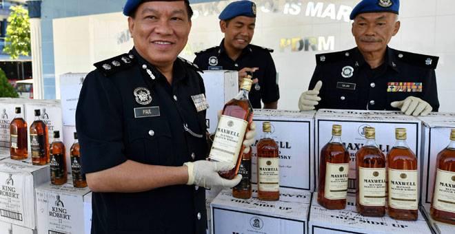 RAMPAS: Paul (kiri) menunjukkan minuman keras tidak bercukai kastam yang dirampas dengan penahanan sebuah pancuan empat roda di Taman Pulai Bayu semalam pada sidang media di Markas Pasukan Polis Marin Wilayah 2 dekat Johor Bahru, semalam. — Gambar Bernama