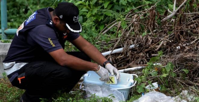 Anggota Unit Forensik memeriksa mayat seorang bayi perempuan yang masih bertali pusat dan dibalut dengan tuala yang ditemui dalam bakul di kawasan longgokan sampah di Jalan Meru Impian 6, Halaman Meru Impian hari ini. - Gambar Bernama