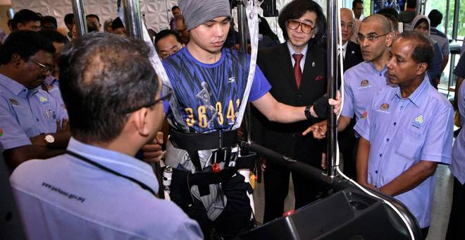 PERTAMA DI MALAYSIA: M. Kula Segaran (kanan) melihat salah satu kaedah rawatan yang dijalani Ong Kai Min, 34, semasa mengadakan lawatan di Pusat Neuro-Robotic Rehabilitation Cybernics selepas majlis perasmian pusat tersebut, semalam. — Gambar Bernama