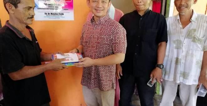 Maszlee menyampaikan kunci rumah dan wang saku kepada penerima bantuan Program Rumah Harapan Md Sallih Esmaildi Kampung Parit Haji Hashim. - Gambar BERNAMA.