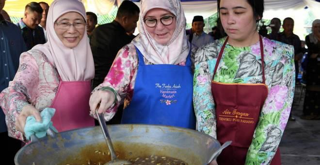 Raja Pemaisuri Agong Tunku Azizah Aminah Maimunah Iskandariah (tengah) bersama anakanda Tengku Puteri Jihan Azizah 'Athiyatullah (kanan) berkenan memasak sendiri bahan-bahan yang akan digunakan untuk membuat bubur lambuk sempena lawatan di Rumah Kanak-kanak Tengku Budriah hari ini. Turut hadir Timbalan Perdana Menteri Datuk Seri Wan Azizah Wan Ismail. - Gambar Bernama