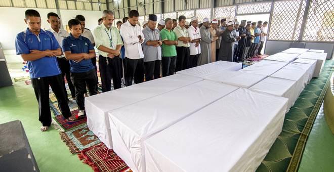 DISEMADI SEMULA: Kesemua 15 jenazah Orang Asli suku Bateq disembahyangkan di Masjid Tengku Muhammad Faiz Petra sebelum dikebumikan dalam satu liang lahad di Tanah Perkuburan Islam Kuala Koh, Gua Musang semalam. — Gambar Bernama
