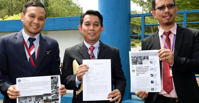 LAPOR POLIS: Jasri (tengah) menunjukkan laporan polis yang dibuat di Ibu Pejabat Polis Daerah Putrajaya berhubung penularan gambar di media sosial yang mendakwa ibu pejabat jabatan itu di sini diserbu pendatang asing untuk mendapatkan status kewarganegaraan. — Gambar Bernama