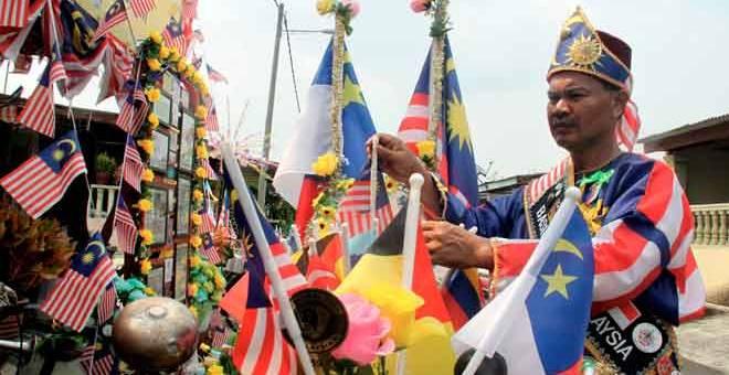 PATRIOTIK: Md Rahim menghias basikal tuanya dengan Jalur Gemilang dan bendera Melaka sebagai rutin wajib setiap kali menjelang sambutan Hari Kebangsaan ketika ditemui Bernama di kediamannya di Taman Pisang Mas Jaya, Gadek, Melaka semalam. — Gambar Bernama