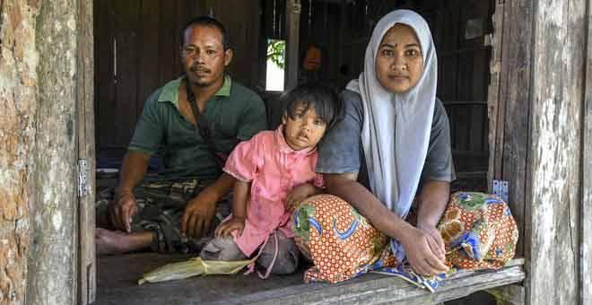 KURANG MAMPU:  Pasangan suami isteri Mohd Zuhaidi (kiri) dan Siti Hamidah bersama anak bongsunya, Nor Syafiya (tengah) tinggal di rumah usang yang disewa mereka di Kampung Tengah dekat Kuala Krai, semalam. — Gambar Bernama