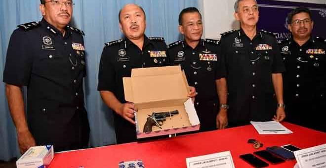 DIRAMPAS: Mohd Kamarudin menunjukkan sepucuk pistol jenis Revolver dan sebutir peluru hidup yang dirampas selepas anggotanya berjaya menahan tiga suspek yang dipercayai terlibat dalam kes samun bersenjata dan bunuh pada sidang media di Ibu Pejabat Polis Daerah Seri Alam, Johor Bahru semalam. — Gambar Bernama