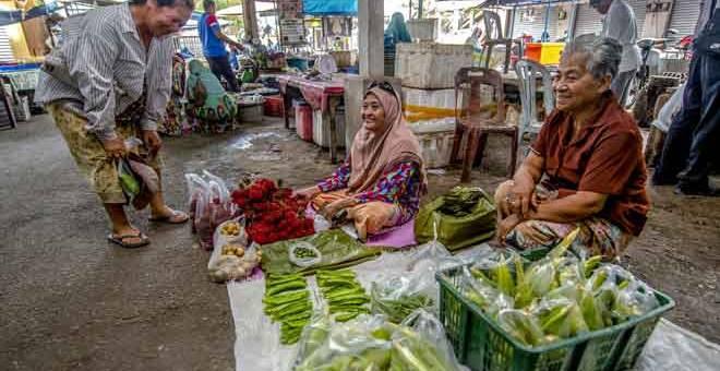 ERAT HUBUNGAN: Peniaga sayur-sayuran Mek Kwan,70, (kanan) keturunan Siam Kelantan berkongsi ruang niaga bersebelahan dengan peniaga Melayu, Che Sopiah Awang, 70, (tengah)  di Pasar Bunohan di Tumpat, semalam. — Gambar Bernama