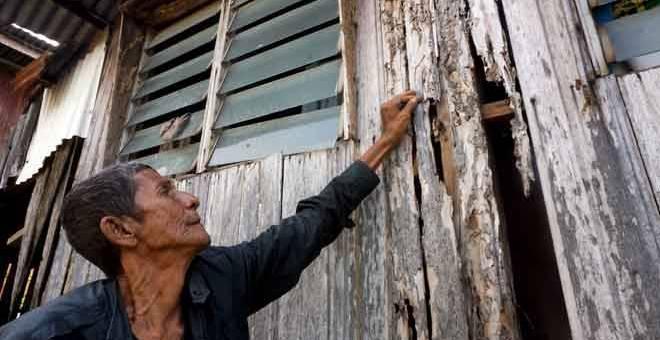REPUT: Nelayan,  Yaacob Ibrahim, 66 menunjukkan dinding yang reput dan berlubang akibat dimakan anai-anai di rumahnya di Lorong Kompleks, Kampung Tengah, Kuala Kedah di Alor Setar, semalam. — Gambar Bernama