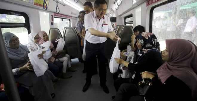 TERIMA KASIH: Menteri Pengangkutan Anthony Loke Siew Fook (tengah) menyampaikan pek makanan kepada penumpang Keretapi Tanah Melayu (KTM) sempena Majlis Perasmian Stesen Nilai, semalam.  — Gambar Bernama