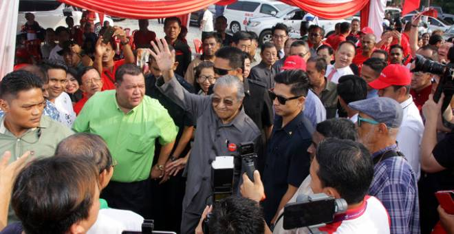 Dr Mahathir  melambaikan tangan kepada orang ramai ketika hadir bersarapan pagi bersama penduduk setempat dan NGO Parlimen Tanjung Piai di Warung 800, Pekan Nanas, hari ini. - Gambar Bernama