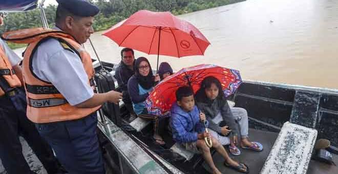 TURUN PADANG: Muhd Nur (kiri) menasihati sebahagian penduduk agar memakai jaket keselamatan ketika menaiki bot pada Program Pertemuan APMM Kelantan Bersama Penduduk di Pulau Muara Sungai Kelantan Untuk Persiapan Banjir semalam. — Gambar Bernama