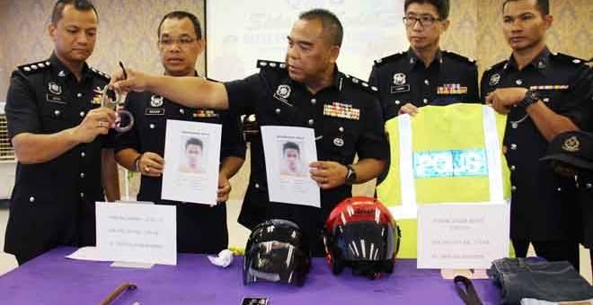 TUNJUK: Osman Mamat (tiga tengah) menunjukkan gari dan gambar suspek yang menyamar anggota polis untuk melakukan samun dalam sidang media di Ibu Pejabat Polis Daerah Taiping semalam.  — Gambar Bernama