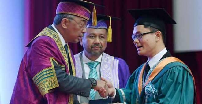 TAHNIAH: Al-Sultan Abdullah berkenan menyampaikan Anugerah Pelajar Diraja kepada Azriel Tan Zhe Khen sempena Majlis Konvokesyen Universiti Malaysia Pahang (UMP) Ke-14 di Kampus Gambang semalam. — Gambar Bernama