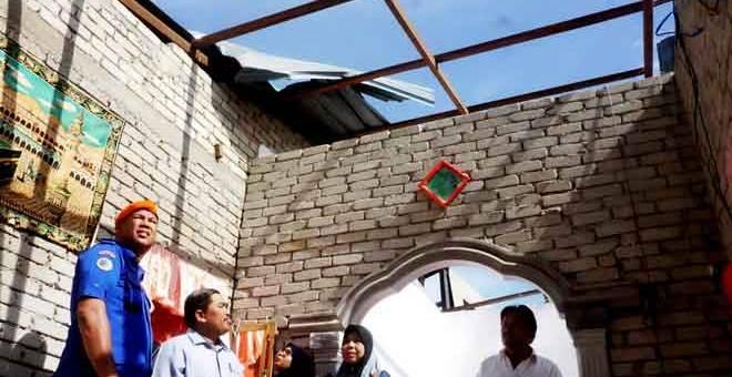 ROSAK: Md Zain (kiri) meninjau kerosakan yang dialami penduduk dalam kejadian puting beliung di Kampung Padang, Mukim Tajar, di Alor Setar semalam. — Gambar Bernama