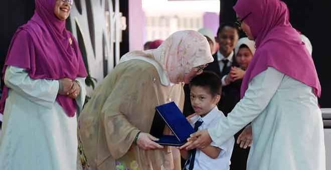 BERKONGSI KASIH: Tunku Azizah berkenan mencium murid Nik Mohamad Afiq Nik Aziz, 7, yang menghidap Sindrom Down pada Majlis Apresiasi Pendidikan Kali ke-16 Sekolah Kebangsaan (SK) Tunku Azizah di Indera Mahkota, Kuantan semalam. — Gambar Bernama