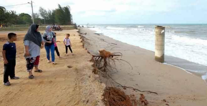 TUMPUAN: Orang ramai melihat sebuah perigi yang kini tidak dapat digunakan berikutan hakisan pantai yang berlaku ketika tinjauan di Pantai Pengkalan Maras, Kuala Nerus semalam. — Gambar Bernama