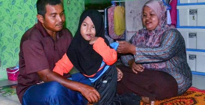 Adik Nur Amni Zahra, 7, Orang Kelainan Upaya (OKU) bersama bapa Khairul Azmi Halim, 34, dan ibu Siti Noraini Shaari, 34, ketika ditemui di rumah mereka di Kampung Chengal Pulas, semalam.