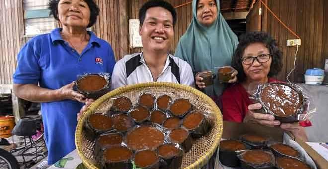 MEMPERKENALKAN: Tan (dua kiri) bersama ibunya Kam Guat Thee (kanan), ibu saudaranya Tan Chui Huai, 65, (kiri) dan jiran, Rosliza Hasan, 49, (dua kiri) menunjukkan kuih bakul yang dihasilkan mereka di Kampung Pantai Kemayang, Tawang di Bachok.  — Gambar Bernama
