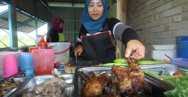 BERJUAL SAMBIL BERAMAL: Salah seorang pekerja sibuk menyediakan menu RM1 di warung milik Zulkifli semalam. — Gambar Bernama