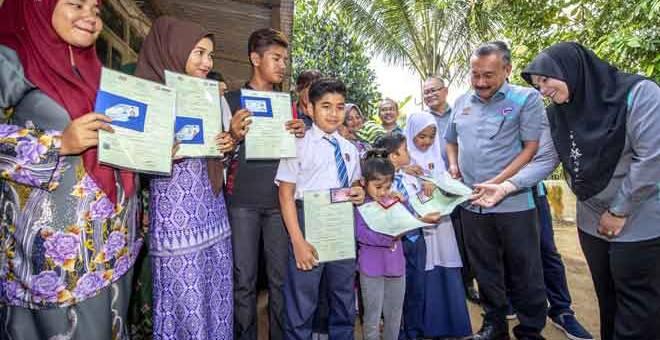 CERIA: Ruslin (dua kanan) menyampaikan dokumen Sijil Kelahiran dan Kad Pengenalan kepada adik Che Danish Haikal, 7, salah seorang daripada lapan beradik yang menerima dokumen Sijil Kelahiran dan Kad Pengenalan di rumah mereka di Kampung Demit Sungai Kubang Kerian, Kota Bharu semalam. Turut hadir, Pengarah JPN Kelantan Asrehan Ab Razak (kanan). Lapan daripada 15 beradik itu menerima dokumen Sijil Kelahiran dan Kad Pengenalan mereka semalam. — Gambar Bernama