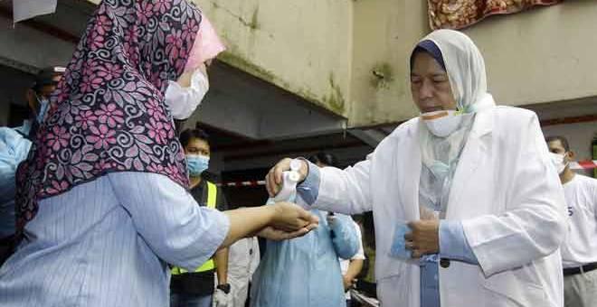 BANTU: Zuraida (kanan) membantu meletakkan cecair pembasmi kuman pada tangan seorang penduduk Emanita Masnur (kiri) sebelum meninjau Operasi Sanitasi COVID-19 di PPR Taman Putra Damai, Lembah Subang 1, Subang Jaya semalam. — Gambar Bernama