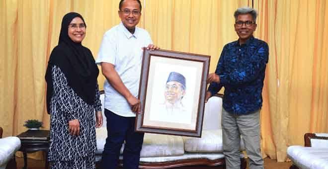CENDERAHATI: Ahmad Samsuri (tengah) menerima cenderahati berupa potret beliau yang diserahkan sendiri oleh pelukisnya Elias Mohd di kediaman Menteri Besar Seri Setia, Kuala Terengganu, semalam. — Gambar Bernama