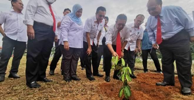 Latiff (tiga kanan) ditemani Henry (kanan), Abdullah, Rubiah dan Salem menanam pokok durian 'Musang King' sebagai gimik perasmian Pejabat Baharu RISDA Sarawak.