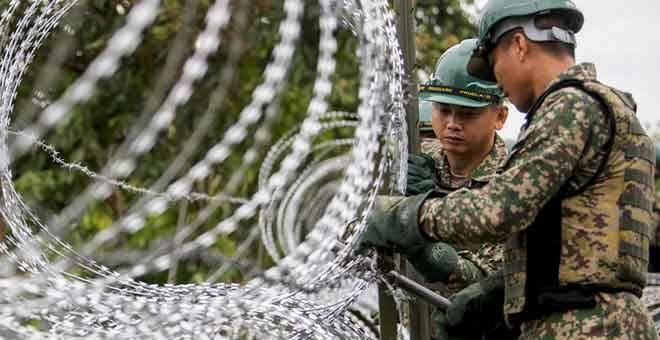 DIKAWAL KETAT: Anggota Skuadron Ke-7 Rejimen Askar Jurutera Diraja melakukan kerja-kerja pemasangan kawat duri bagi membendung kemasukan PATI dan aktiviti penyeludupan antara sempadan Malaysia-Thailand menerusi Ops Benteng COVID-19 di Pangkalan Haram Pok Nik, Jeram Perdah, dekat Pasir Mas semalam. — Gambar Bernama