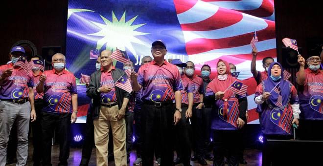 LAGU PATRIOTIK: Wan Rosdy (depan) bersama barisan kepimpinan kerajaan negeri Pahang mengibarkan Jalur Gemilang sambil menyanyikan lagu patriotik pada Majlis Sambutan Hari Malaysia 2020 Peringkat Negeri Pahang di Dewan Institut Kemahiran Belia Negara (IKBN) Pekan, semalam. — Gambar Bernama