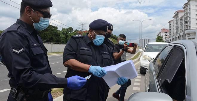 PERIKSA: Shanmugamoorthy memeriksa dokumen salah seorang pengguna jalan raya ketika memantau orang ramai terhadap pematuhan sekatan jalan raya sekitar daerah Sentul, Kuala Lumpur susulan pelaksanaan Perintah Kawalan Pergerakan Bersyarat (PKPB) semalam. — Gambar Bernama
